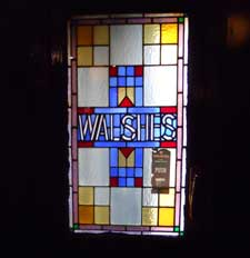 The glass door of Walshe's pub in Stoneybatter